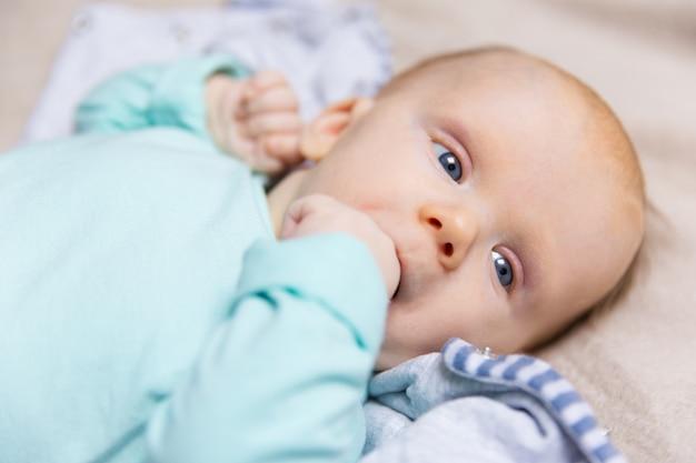 Primer plano de pensativo dulce bebé con el dedo en la boca