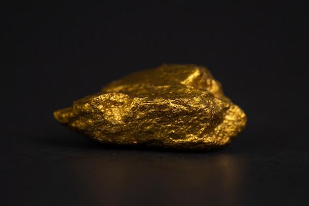 Primer plano de pepita de oro o mineral de oro en negro