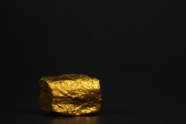 Primer plano de pepita de oro o mineral de oro sobre fondo negro