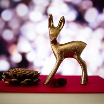Primer plano de una pequeña figura de ciervo y una piña en un libro con un fondo borroso y luces bokeh