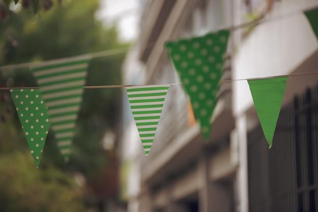 Primer plano de pequeñas banderas verdes con puntos blancos y rayas en el día de san patricio