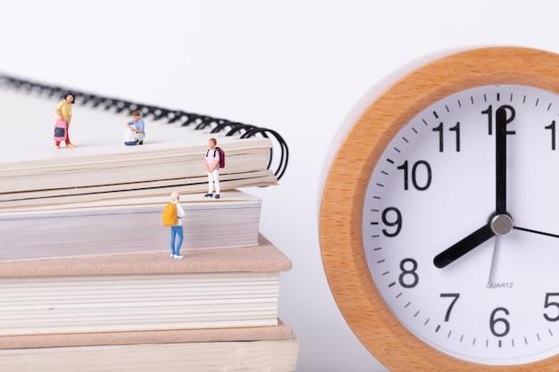 Primer plano de pequeñas figurillas de estudiantes de pie sobre libros de texto junto a un reloj