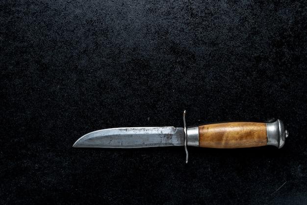 Primer plano de un pequeño cuchillo afilado con mango marrón sobre un fondo negro