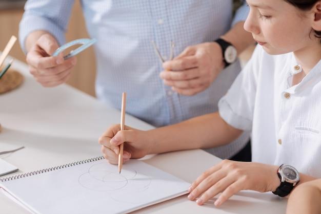 El primer plano de un pequeño y lindo colegial dibujando círculos con un lápiz mientras su padre está de pie junto a él y está listo para entregarle un transportador y un par de brújulas.