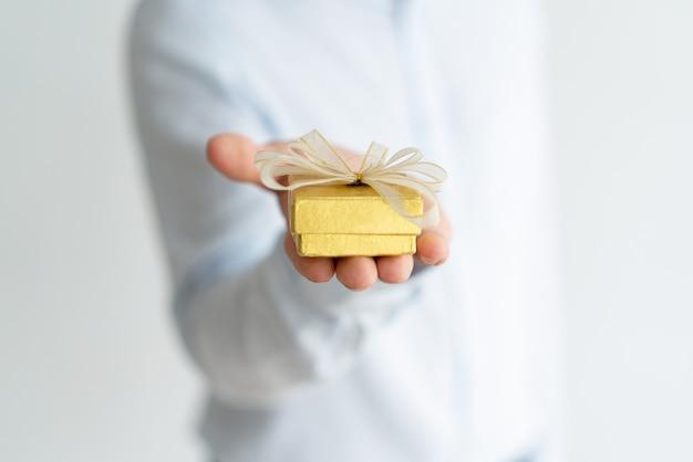 Primer plano de un pequeño regalo en mano masculina