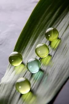 Primer plano de perlas de baño en hoja verde