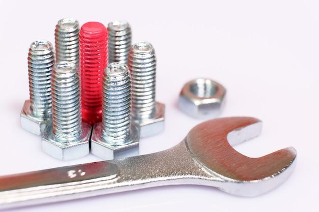 Primer plano de un perno rosa n un grupo de tornillos metálicos galvanizados, llave y tuerca