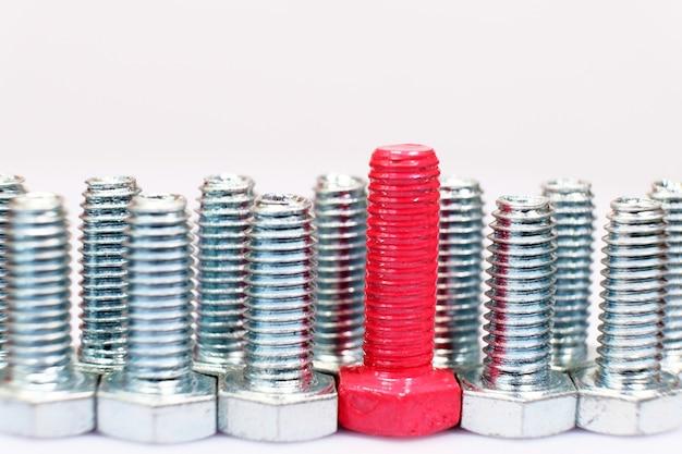 Primer plano de un perno rosa n un grupo de tornillos metálicos galvanizados
