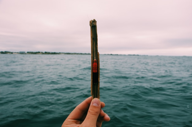 Primer plano de una persona con un cebo de pesca con un mar borroso y un cielo nublado