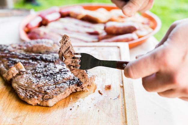 Primer plano de una persona comiendo bistec en tajadera con tenedor y cuchillo