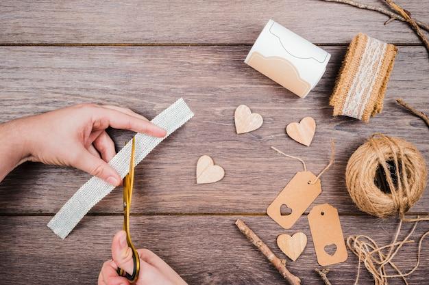 Primer plano de una persona cortando el cordón con un cuchillo en el escritorio de madera