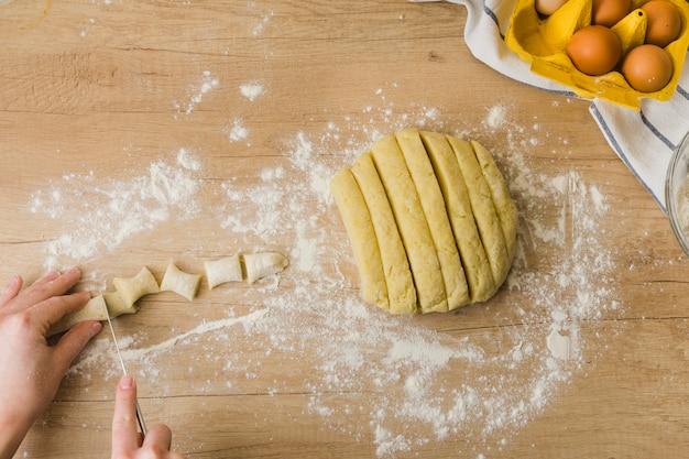 Primer plano de una persona cortando la masa para preparar los ñoquis de pasta italiana fresca