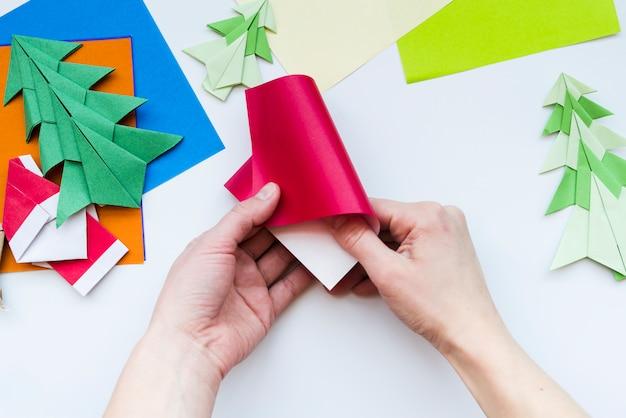Primer plano de una persona haciendo origami navideño sobre fondo blanco