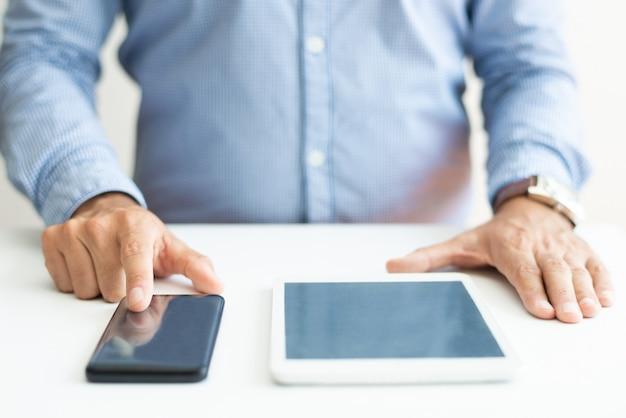Primer plano de la persona de negocios usando teléfono inteligente y tableta