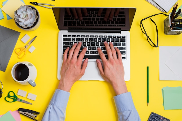 Primer plano de una persona que escribe en la computadora portátil sobre el escritorio de oficina mínimo creativo