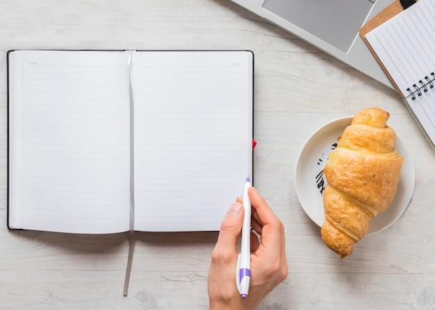 Primer plano de una persona que escribe en el diario con lápiz y croissant en un plato sobre el escritorio de madera