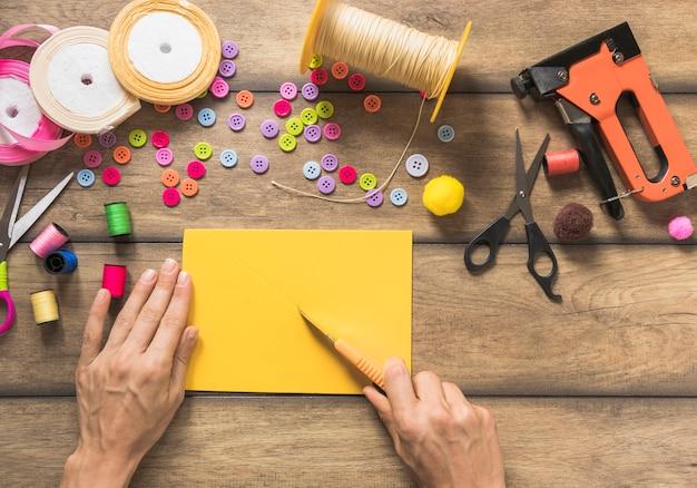 Primer plano de una persona que hace tarjetas de felicitación con carrete; botones y cintas