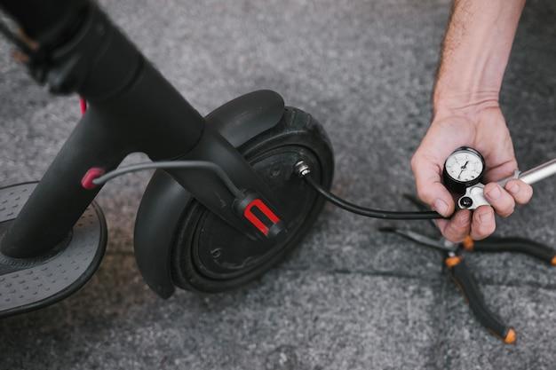 Primer plano de la persona que infla el neumático de e-scooter
