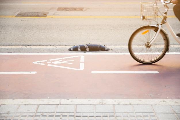Primer plano de una persona que monta la bicicleta en una carretera con un signo de advertencia de triángulo