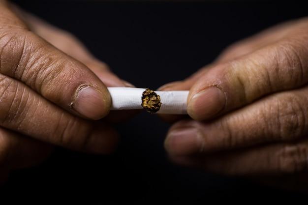 Primer plano de una persona que rompe un cigarrillo por la mitad - concepto de dejar los malos hábitos