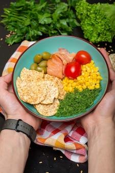 Primer plano de una persona que sostiene un plato de ensalada con salmón, galletas saladas y verduras bajo las luces