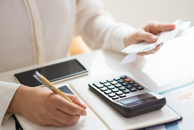 Primer plano de la persona que tiene facturas y las calcula