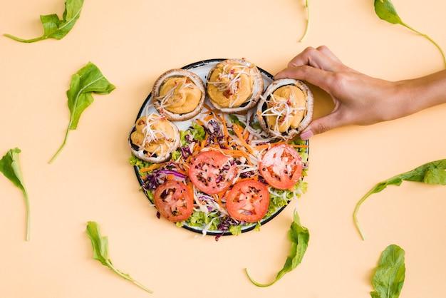 Primer plano de una persona que toma tapas de champiñones rellenas de cremas en un plato sobre el fondo beige