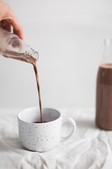 Primer plano de una persona que vierte batido de chocolate en taza blanca