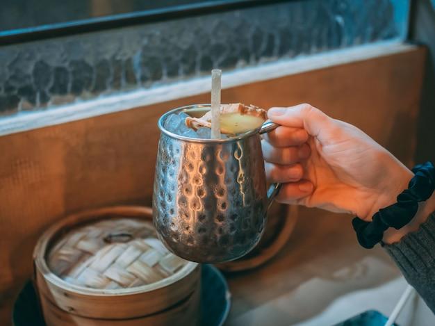 Primer plano de una persona sosteniendo una bebida asiática de jengibre