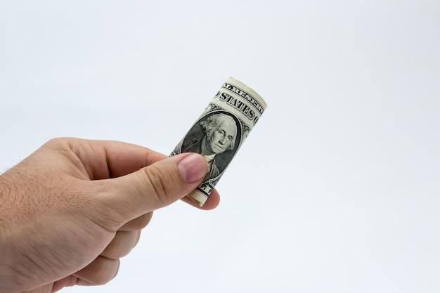 Primer plano de una persona sosteniendo un billete de un dólar sobre un fondo blanco.