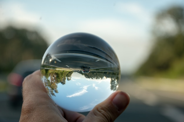 Primer plano de una persona sosteniendo una bola de cristal con el reflejo de los árboles