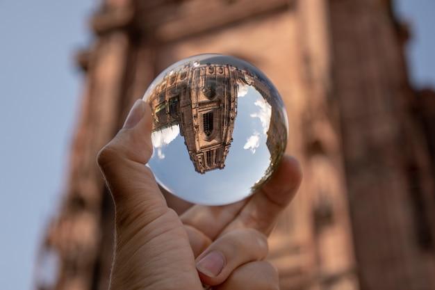 Primer plano de una persona sosteniendo una bola de cristal con el reflejo de edificios históricos