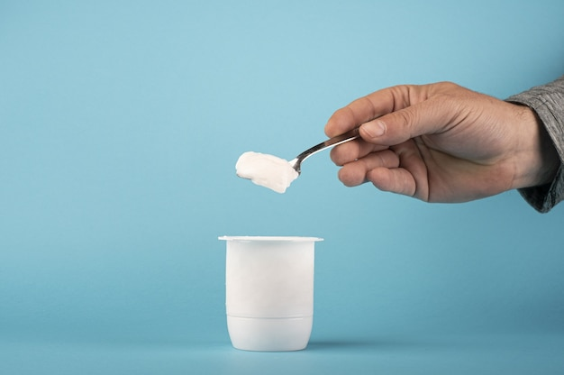 Primer plano de una persona sosteniendo una cuchara con yogur blanco sobre un fondo azul.