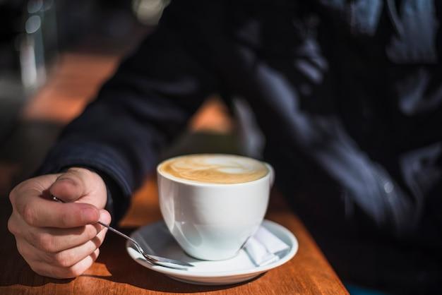 Primer plano de una persona con una taza de café caliente en la mesa