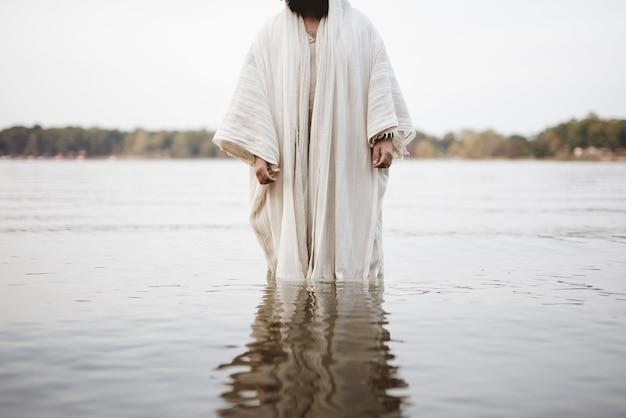 Primer plano de una persona vestida con una túnica bíblica de pie en el agua