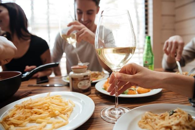 Primer plano de personas bebiendo vino y comiendo pasta en la mesa