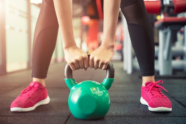 Primer plano de personas ejercicio con pesas rusas en el gimnasio entrenamiento deportivo y fitness