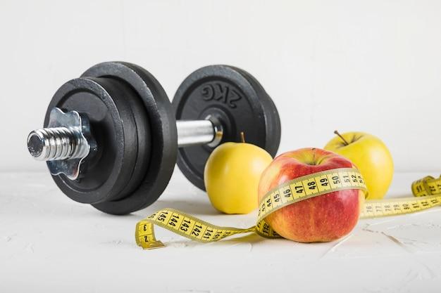 Primer plano de pesas y frutas con cinta métrica sobre fondo blanco