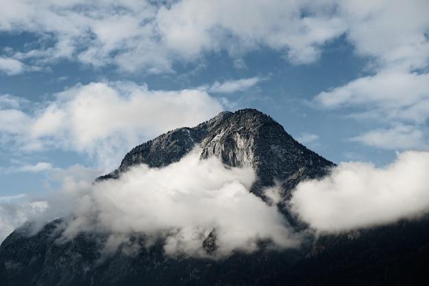 Primer plano de un pico de montaña parcialmente cubierto por nubes