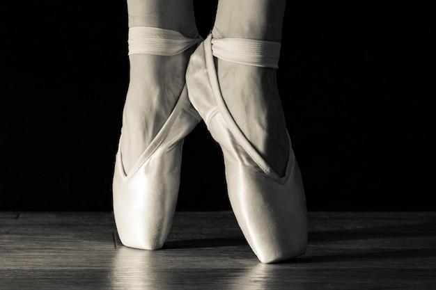 Primer plano de las piernas de la bailarina clásica en pointes sobre el negro