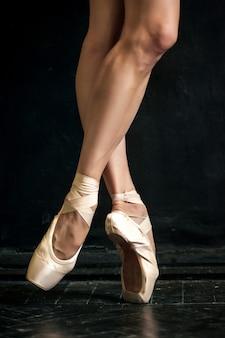 Primer plano de las piernas de la bailarina en pointes sobre el piso de madera negro