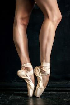 Primer plano de las piernas de la bailarina y puntas en el piso de madera negra