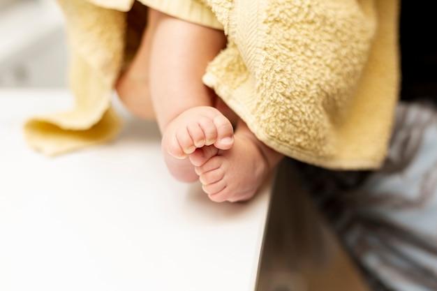 Primer plano de las piernas del bebé con una toalla amarilla