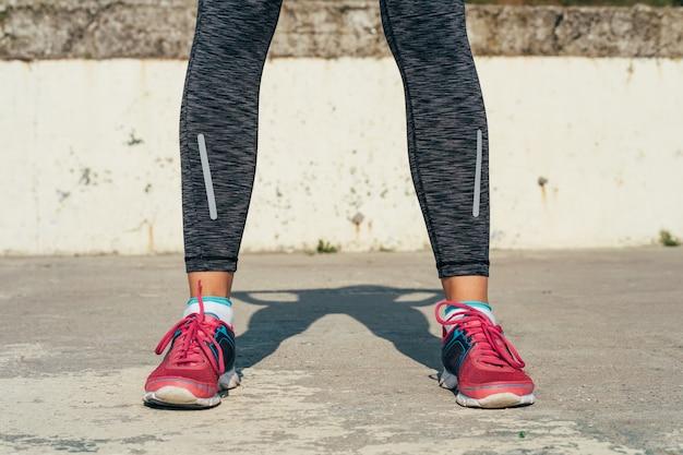 Primer plano de las piernas femeninas atléticas en zapatillas de deporte rojas en un cojín concreto al aire libre en luz del sol