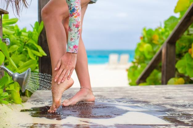 Primer plano de piernas femeninas bajo una ducha de playa en el caribe