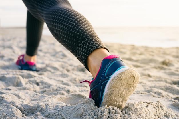 Primer plano de las piernas femeninas en medias y zapatillas de deporte durante el ejercicio de la mañana en la playa