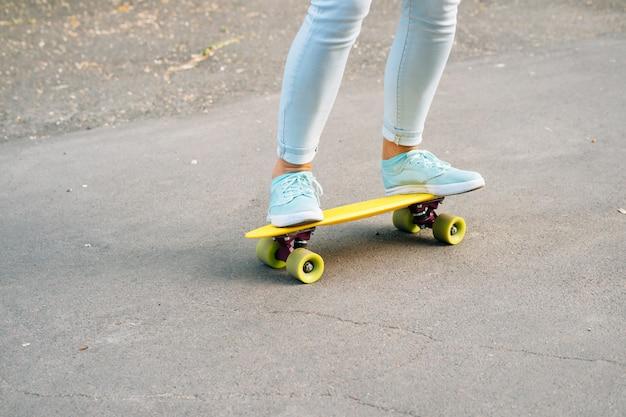 Primer plano de piernas femeninas en vaqueros y zapatillas de deporte montando una patineta en la carretera