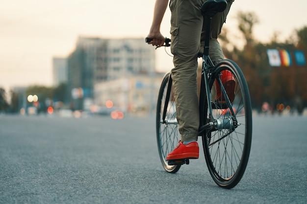 Primer plano de las piernas del hombre casual en bicicleta clásica en la carretera de la ciudad