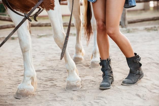 Primer plano de las piernas de la mujer y el caballo caminando juntos en el rancho