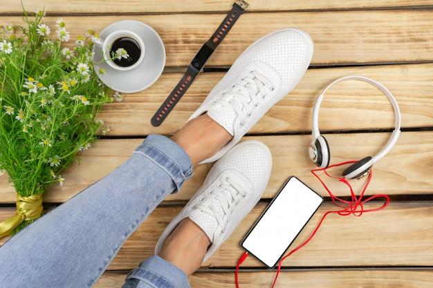 Primer plano de las piernas de la mujer en elegantes zapatos con auriculares